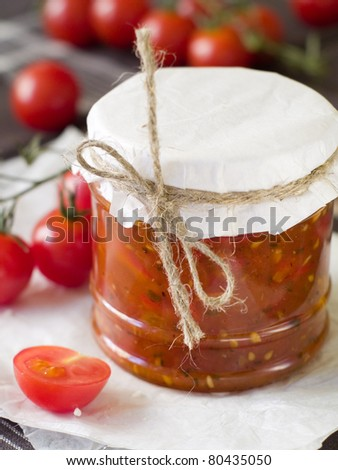 Tomato jam with pepper and garlic in glass jar. Selective focus, shallow doff