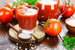 Tomato juice in a glass jug on a wooden table