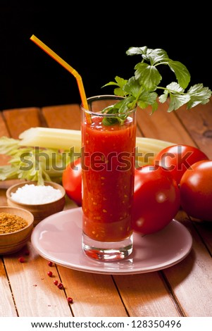 tomato juice with celery on table with black background