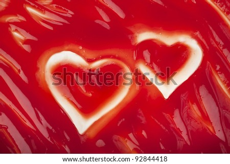 Tomato ketchup sauce texture with hearts background