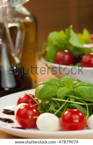 Tomato, mozzarella, rocket salad with olive oil and balsamic vinegar dressing and basil garnish shot in golden sunshine