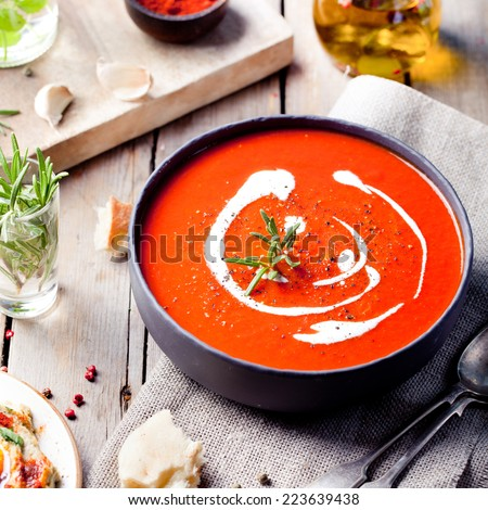 Tomato, red pepper soup, sauce with olive oil, rosemary and smoked paprika on a wooden background.