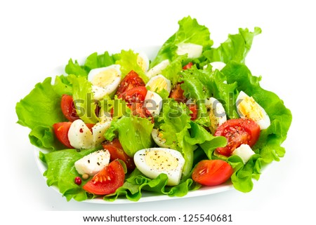 Tomato salad, quail eggs and mozzarella isolated on white background