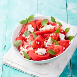 Tomato salad with basil, cheese, olive oil and garlic dressing Blue wooden background