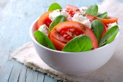 Tomato salad with spinach, cottage cheese, olive oil and pepper on blue wooden background.