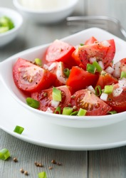 Tomato salad with spring onion and coriander seeds. Home made food. Symbolic image. Concept for a tasty and healthy meal. Bright wooden background. Close up