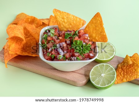 Tomato salsa or salsa Roja traditional Mexican sauce with ingredients for making on a light green background. homemade recipe Pico de Gallo with nachos. Selective focus. Foto stock ©
