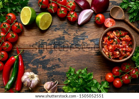 Tomato salsa (salsa roja) - traditional mexican sauce  with ingredients for making on a wooden background.Top view with copy space.  Stock photo ©