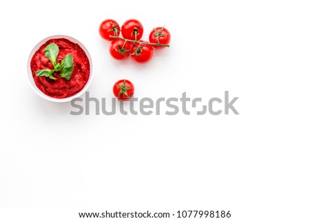 Tomato sauce in bowl with green basil near cherry tomatoes on white background top view copy space #1077998186