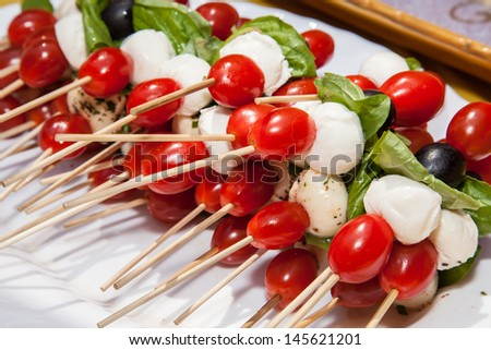 Tomato skewers piled high on a platter, dressed up with a little basil oil.b