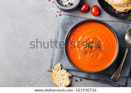 tomato soup in a black bowl on...