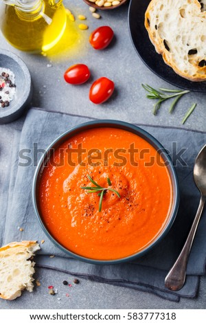 Tomato soup in a black bowl on grey stone background. Top view. Copy space.