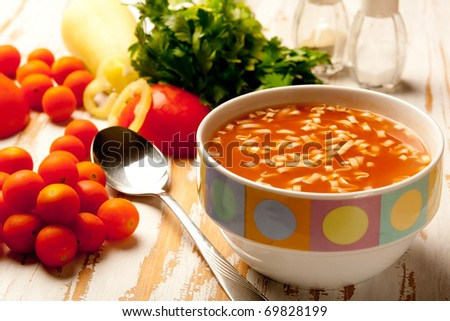 Tomato soup in a bowl with fresh ingredients and herbs