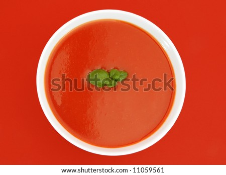 tomato soup in white bowl, red background