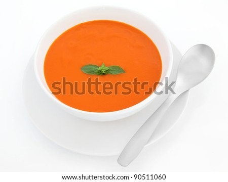 Tomato soup with basil herb leaf in a porcelain bowl with plate and stainless steel spoon isolated over white background.