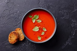 Tomato soup with basil in a bowl. Dark background. Close up. Top view.