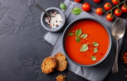 Tomato soup with basil in a bowl. Dark background. Copy space. Top view.
