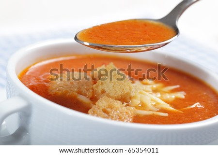 Tomato soup with croutons and shredded cheese