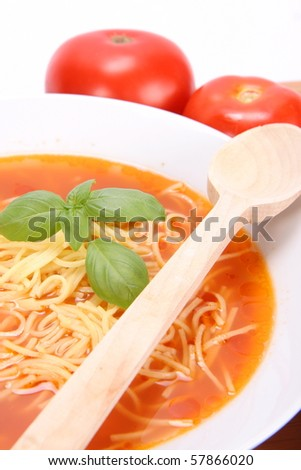 Tomato soup with macaroni decorated with basil with a wooden spoon and fresh tomatoes around it