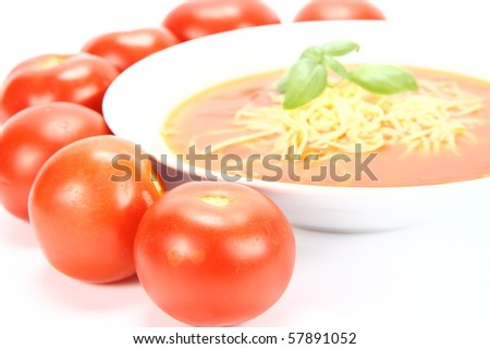 Tomato soup with macaroni decorated with basil with fresh tomatoes around it