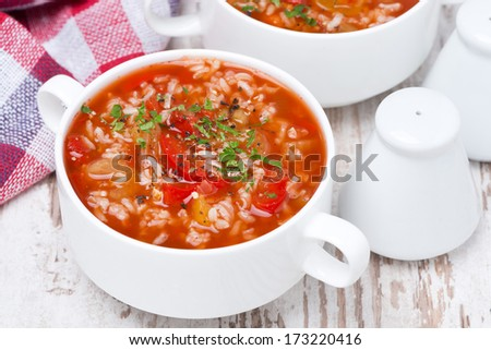 tomato soup with rice and vegetables in a bowl, top view, horizontal