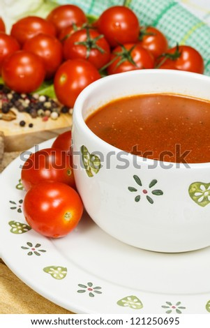Tomato soup with tomatoes in background