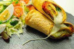 Tomato tortilla wrap with mozzarella cheese,  tomatoes, rocket, basil pesto,  and mix salad, tasty food