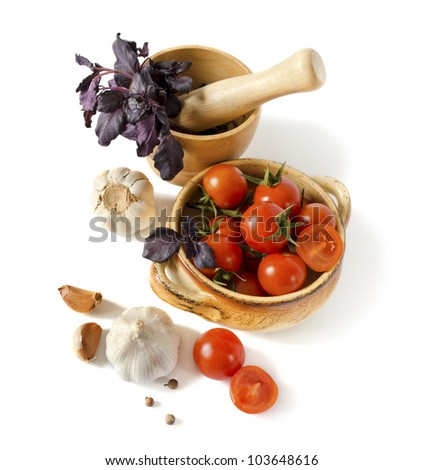 Tomatoes, a basil in a mortar, garlic and spices are isolated on a white background