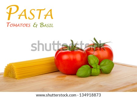 Tomatoes, basil and uncooked spaghetti on a cutting board isolated on white
