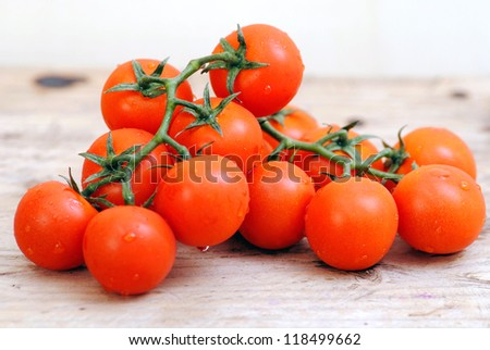 Tomatoes.Branch of cherry tomatoes on white wood rustic background.Organic food. Light, detox food - stock photo