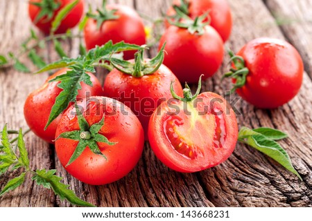 Tomatoes, cooked with herbs for the preservation on the old wooden table.