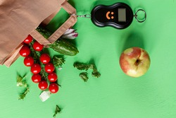 tomatoes, cucumbers, some lettuce, apple, counterweight pulley and a paper bag on green background