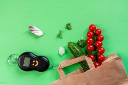 tomatoes, cucumbers, some lettuce, counterweight pulley and a paper bag on green background