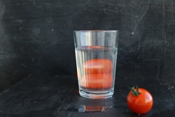 Tomatoes Distorted Through Liquid and Glass. Distorted glass of water. distorted Vegetables seen through a glass of water.