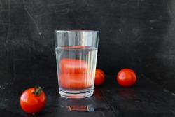 Tomatoes Distorted Through Liquid in Glass. Distorted glass of water. distorted Tomato seen through a glass of water.