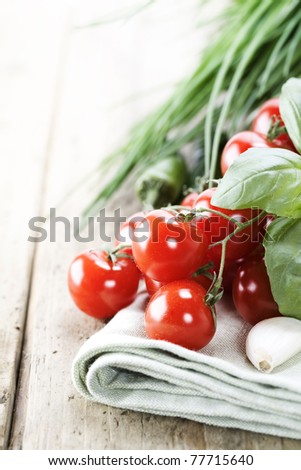 Tomatoes, garlic, chives and chili peppers on a wooden table top