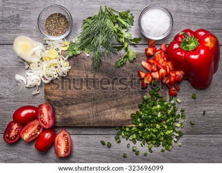 tomatoes, leek parsley and dill chopped red pepper green onion on a wooden cutting board on wooden background top view #323696099