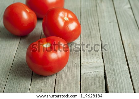 tomatoes on old, weathered wooden background