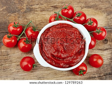 tomatoes paste with ripe tomatoes on wooden tables