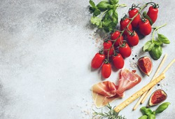 Tomatoes, prosciutto and fresh basil. Mediterranean appetizers table concept. Overhead view
