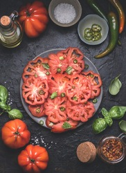 Tomatoes salad with Italian Oxheart tomatoes (Cuore di Bue), olives oil , basil and spacy papper. Simple plate of  vegetarian salad, cutlery and ingredients on dark rustic background, flat lay