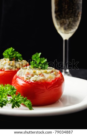 Tomatoes stuffed with cheese and decorated with fresh herbs (shallow dof)