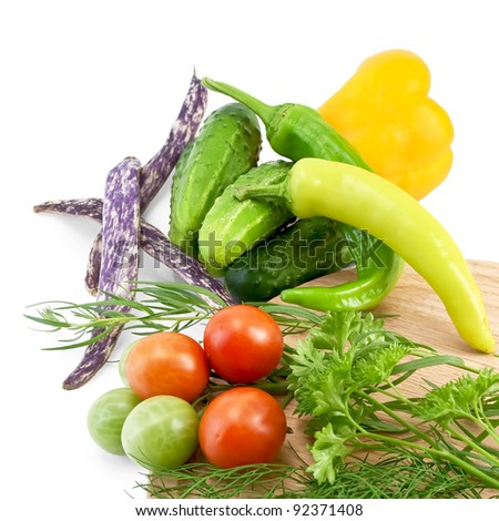 Tomatoes, two sharp pepper, parsley, dill, tarragon on a wooden board round, cucumbers, bell peppers, three green beans isolated on white background
