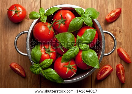Tomatoes with basil in colander on wooden table background. Food composition. Top view