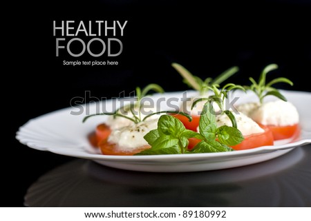 Tomatoes with mozzarella and rosemary on white plate isolated on black background