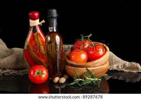 Tomatos and garlic in wooden plate on black background.