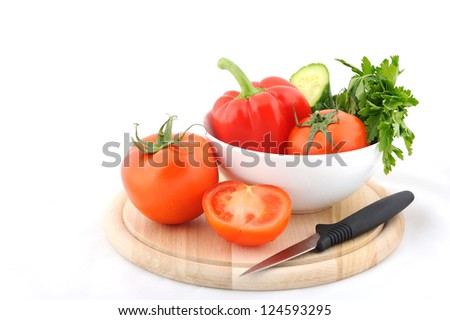tomatos and paprika in white plate on wooden cutting board