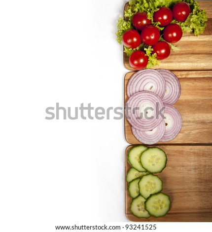 Tomatos, onions and cucumbers on boards and white background