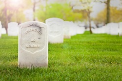 Tombstone of unknown soldier on the cemetery grass ground with other graves on background