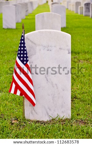 tombstone on a national cemetery with the american flag